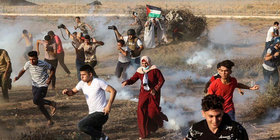 متظاهرون فلسطينيون وصحفيون يفرون من قنابل غاز المسيلة للدموع
